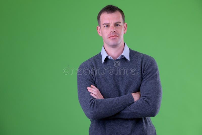 Retrato del hombre de negocios con los brazos cruzados contra fondo verde fotografía de archivo libre de regalías