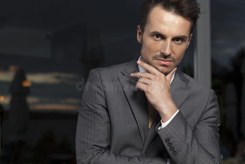 Retrato del hombre de negocios confiado con la mano en la barbilla en oficina fotos de archivo libres de regalías