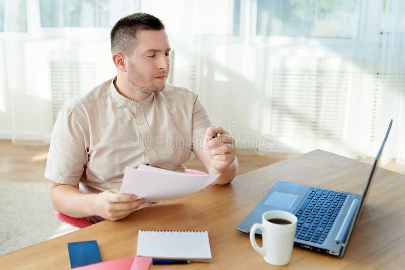 Retrato del hombre de negocios confiado joven que se sienta en el escritorio de madera y que trabaja con los documentos y ordenad imagen de archivo