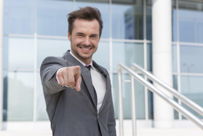 Retrato del hombre de negocios confiado que señala en usted el edificio de oficinas del exterior fotografía de archivo libre de regalías