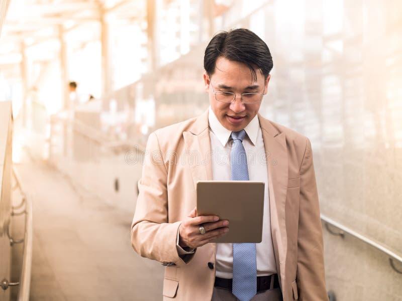 Retrato del hombre de negocios elegante en un traje y vidrios que llevan foto de archivo
