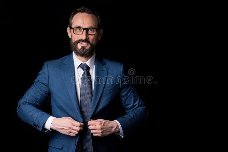 Retrato del hombre de negocios envejecido centro barbudo confiado en las lentes que abotonan la chaqueta del traje imagen de archivo libre de regalías