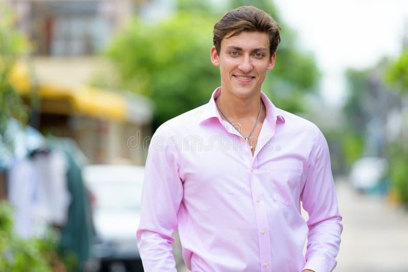 Retrato del hombre de negocios hermoso joven feliz que sonríe al aire libre imagen de archivo libre de regalías