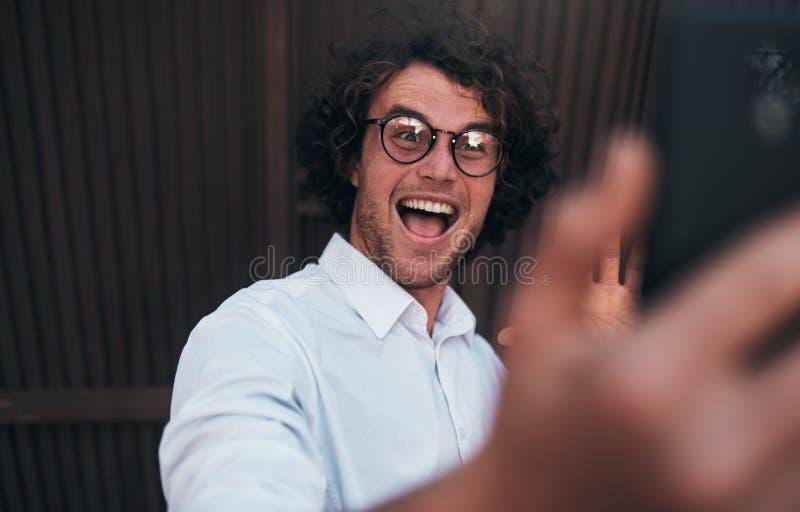 Retrato del hombre de negocios hermoso joven feliz que toma el autorretrato con su teléfono elegante al aire libre El llevar sonr fotos de archivo