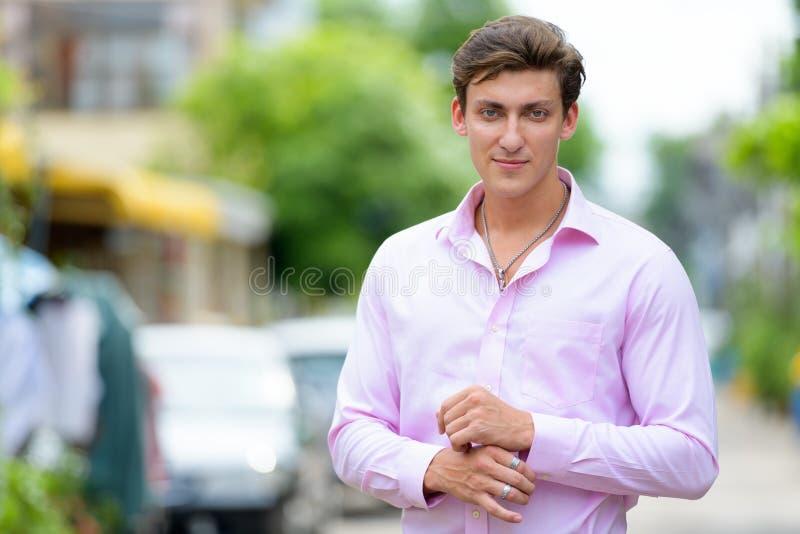 Retrato del hombre de negocios hermoso joven que lleva la camisa rosada al aire libre imagen de archivo