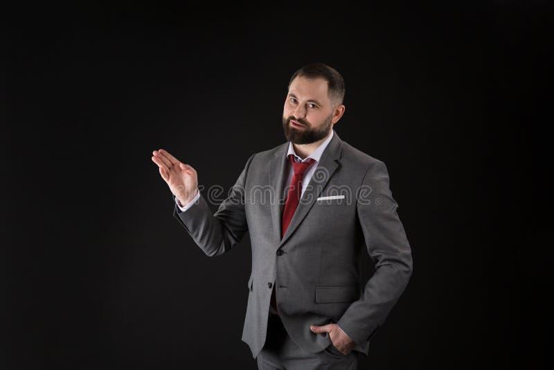 Retrato del hombre de negocios hermoso joven que presenta gesto en fondo negro fotografía de archivo libre de regalías