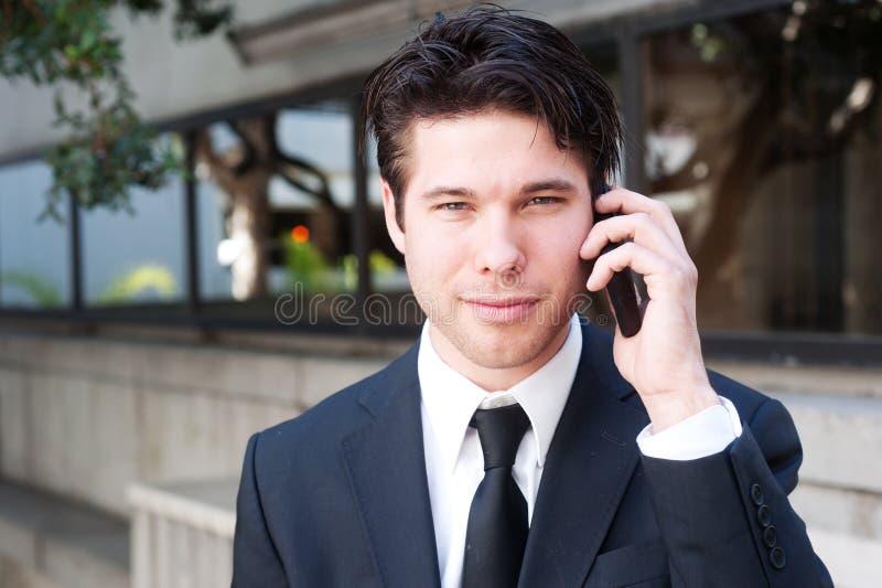 Retrato del hombre de negocios hermoso, joven que usa la célula fotografía de archivo