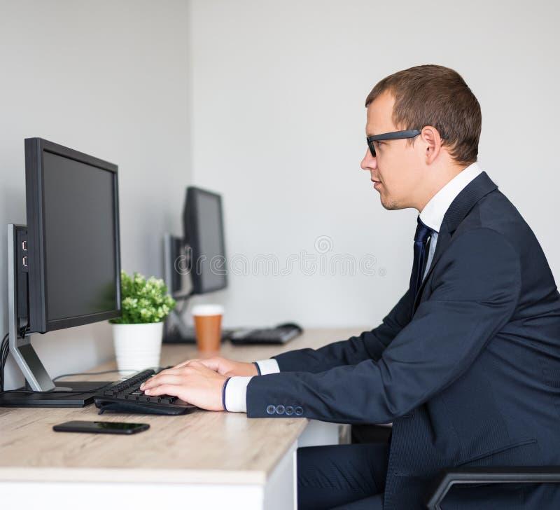 Retrato del hombre de negocios hermoso joven usando el ordenador en oficina moderna fotos de archivo