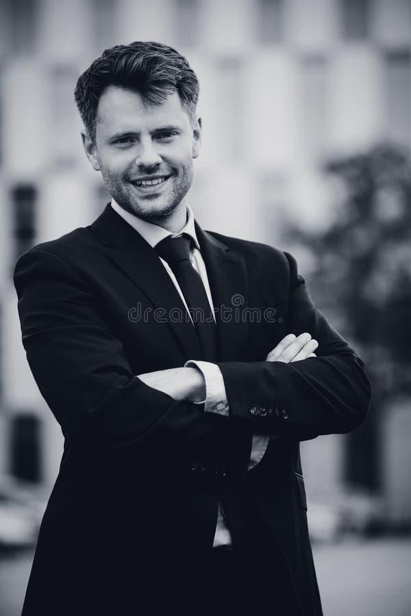 Retrato del hombre de negocios hermoso que se coloca con los brazos cruzados imagen de archivo libre de regalías