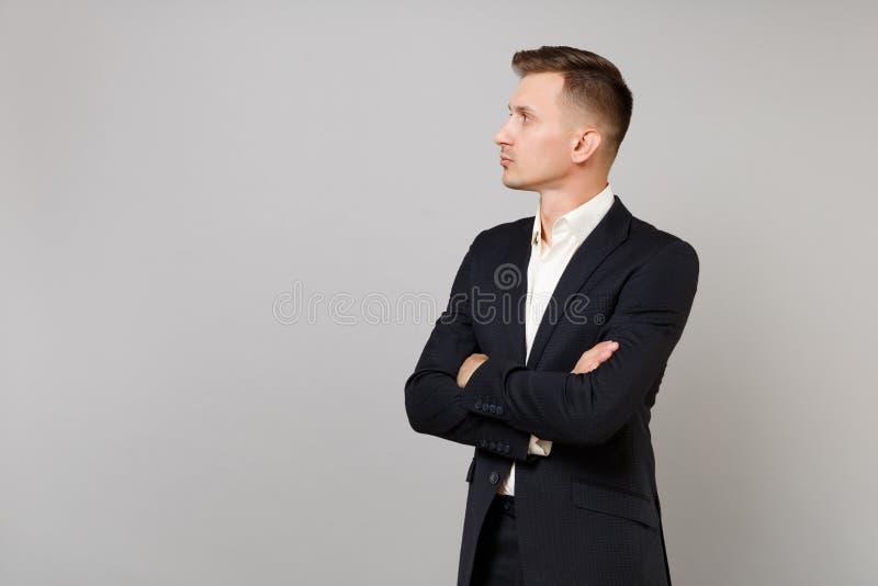 Retrato del hombre de negocios joven en el traje negro clásico, camisa que mira a un lado, llevando a cabo las manos dobladas ais imagen de archivo libre de regalías