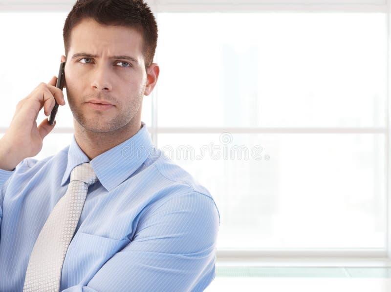Retrato del hombre de negocios joven en la llamada foto de archivo