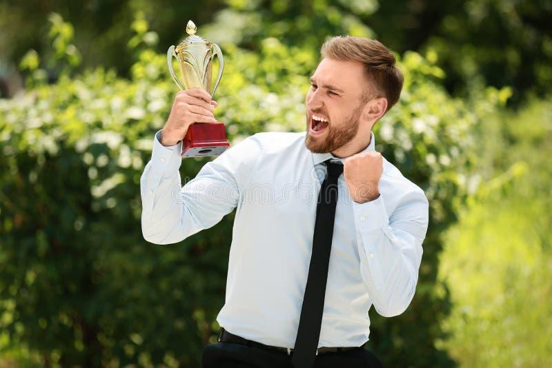 Retrato del hombre de negocios joven feliz con la taza del trofeo del oro imagen de archivo libre de regalías