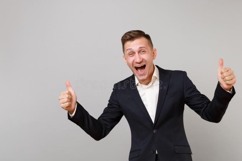 Retrato del hombre de negocios joven feliz en el traje negro clásico, pulgar de la demostración de la camisa encima del griterío  imagen de archivo