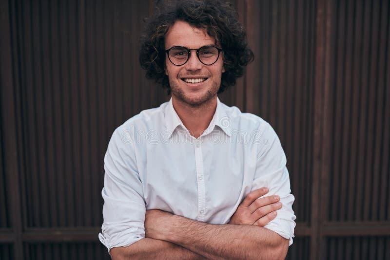 Retrato del hombre de negocios joven hermoso feliz con los vidrios, sonrisa, presentando al aire libre Estudiante masculino que p imagen de archivo libre de regalías