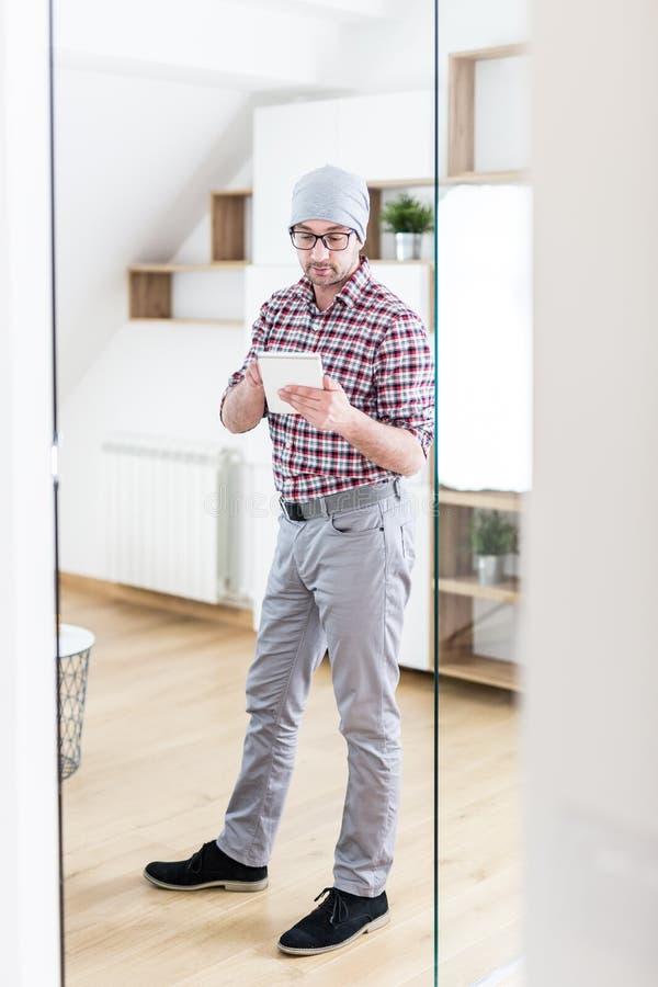 Retrato del hombre de negocios joven de moda que celebra la tableta digital en la oficina moderna foto de archivo