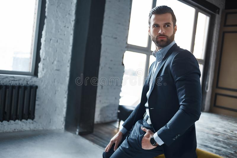 Retrato del hombre de negocios joven de moda y elegante en un traje que está mirando seriamente a un lado y está pensando en trab fotos de archivo libres de regalías