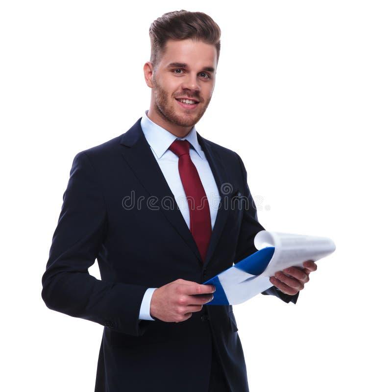 Retrato del hombre de negocios joven que comprueba sus ficheros y sonrisa fotos de archivo