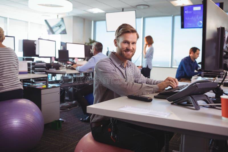 Retrato del hombre de negocios joven que trabaja en el escritorio mientras que se sienta en bola del ejercicio fotos de archivo libres de regalías