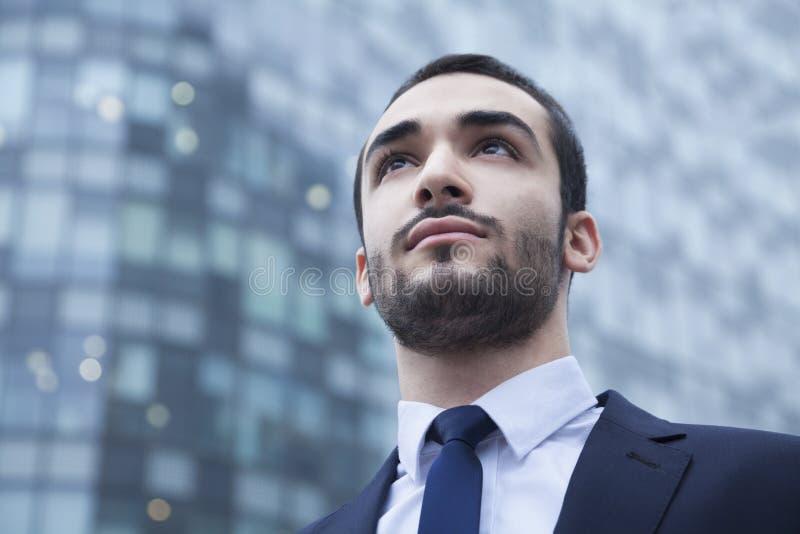 Retrato del hombre de negocios joven serio que mira para arriba, al aire libre, el distrito financiero imagen de archivo
