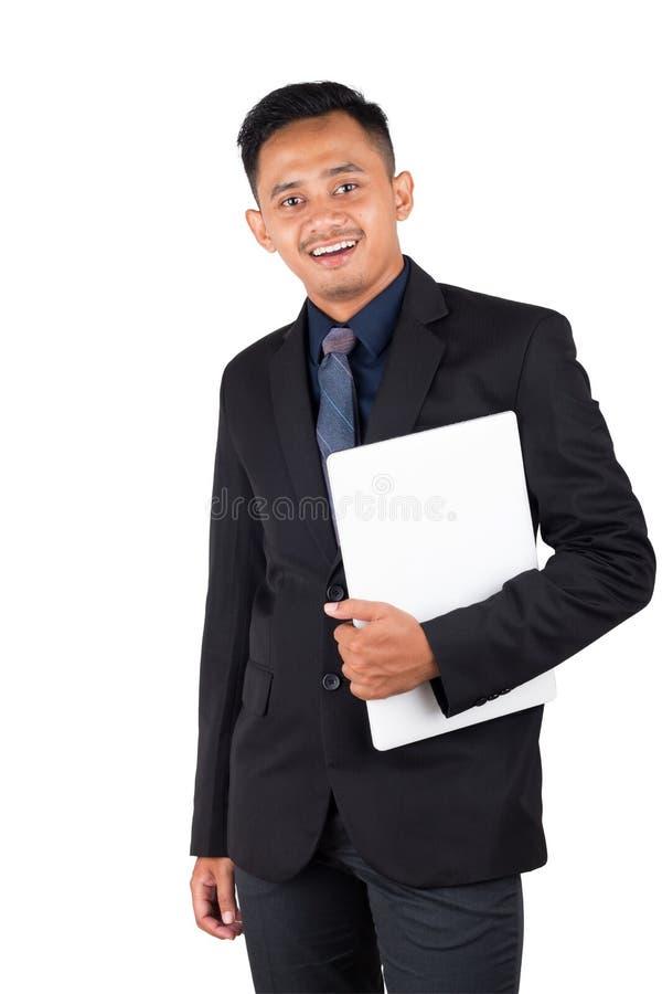 Retrato del hombre de negocios joven sonriente feliz mientras que ordenador portátil en su mano imagenes de archivo
