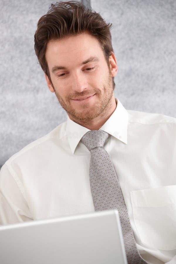 Retrato del hombre de negocios joven usando la sonrisa de la computadora portátil foto de archivo