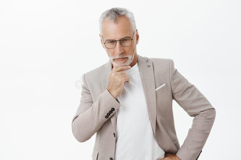 Retrato del hombre de negocios maduro atractivo rico y pensativo inteligente con la barba gris del frotamiento del pelo que mira  fotografía de archivo libre de regalías