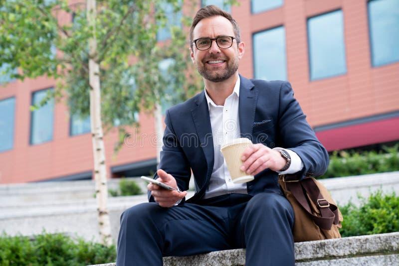 Retrato del hombre de negocios maduro With Mobile Sitting en el edificio de oficinas exterior fotos de archivo