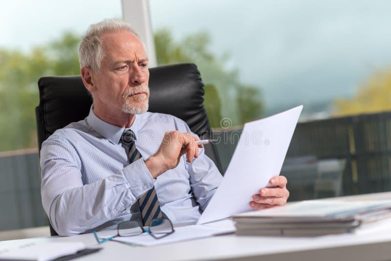 Retrato del hombre de negocios maduro que comprueba un documento foto de archivo libre de regalías