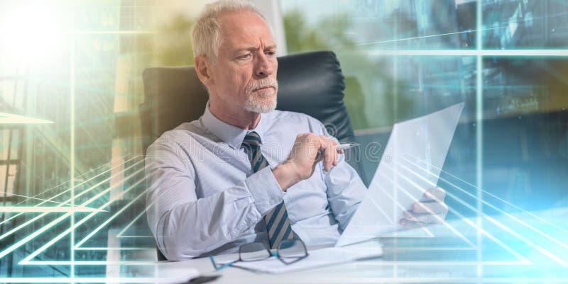 Retrato del hombre de negocios maduro que comprueba un documento; exp múltiple foto de archivo libre de regalías