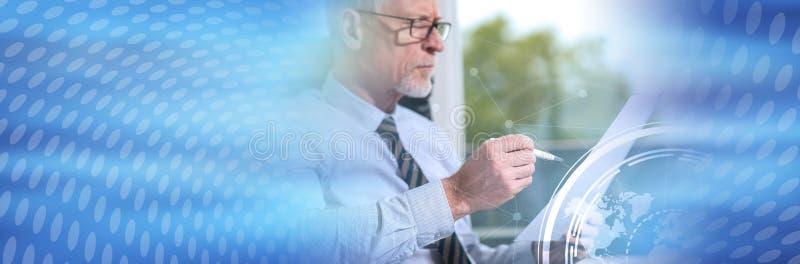 Retrato del hombre de negocios maduro que comprueba un documento, sobrepuesto con las cartas Bandera panor?mica foto de archivo libre de regalías