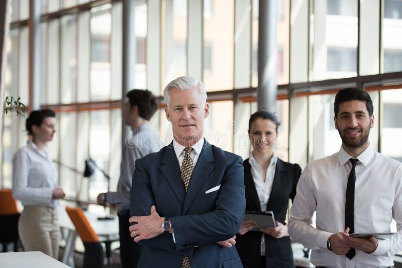 Retrato del hombre de negocios mayor como líder con el grupo de personas i imagenes de archivo
