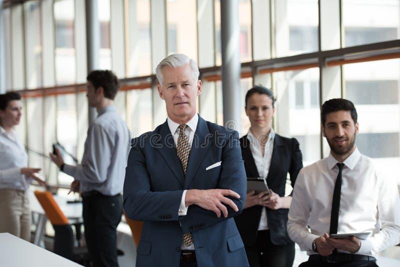 Retrato del hombre de negocios mayor como líder con el grupo de personas i fotografía de archivo