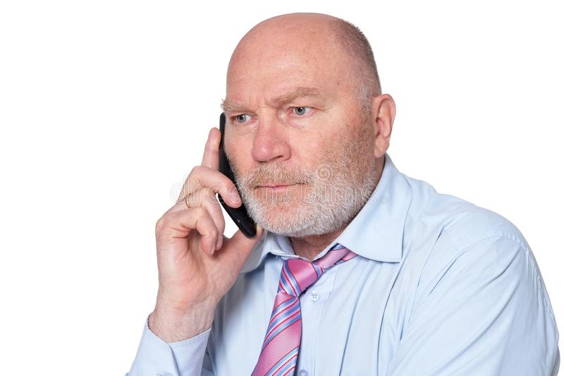 Retrato del hombre de negocios mayor con el teléfono móvil en el fondo blanco imagen de archivo libre de regalías