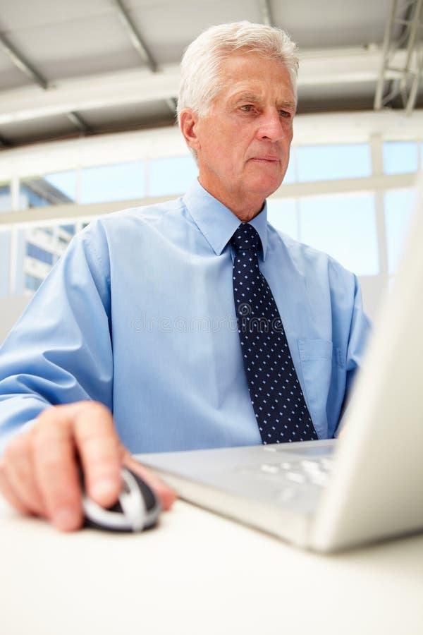 Retrato del hombre de negocios mayor usando la computadora portátil fotos de archivo libres de regalías