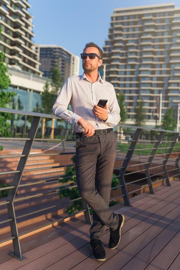 Retrato del hombre de negocios moderno que sostiene el teléfono móvil contra edificios del negocio fotos de archivo