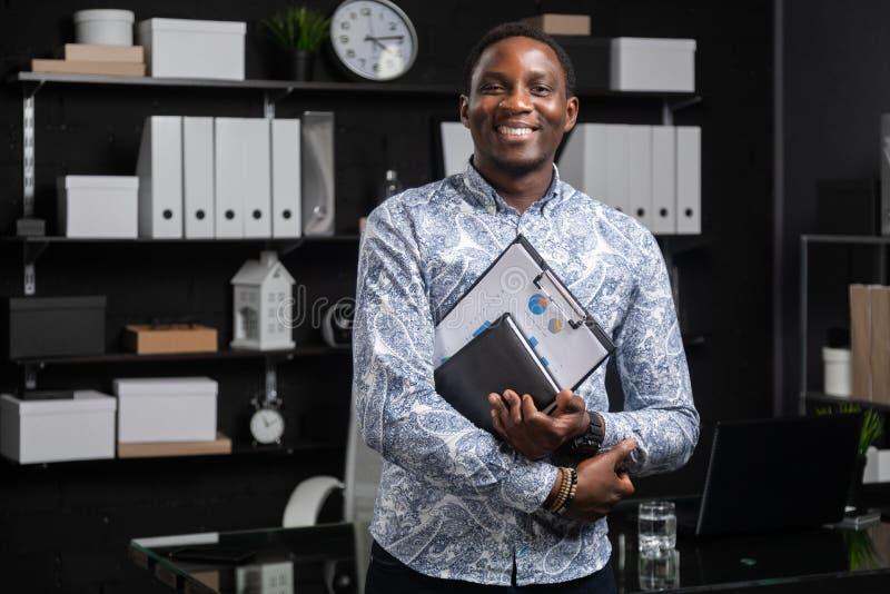 Retrato del hombre de negocios negro joven con los documentos financieros en sus manos que se colocan cerca de la tabla en oficin foto de archivo libre de regalías