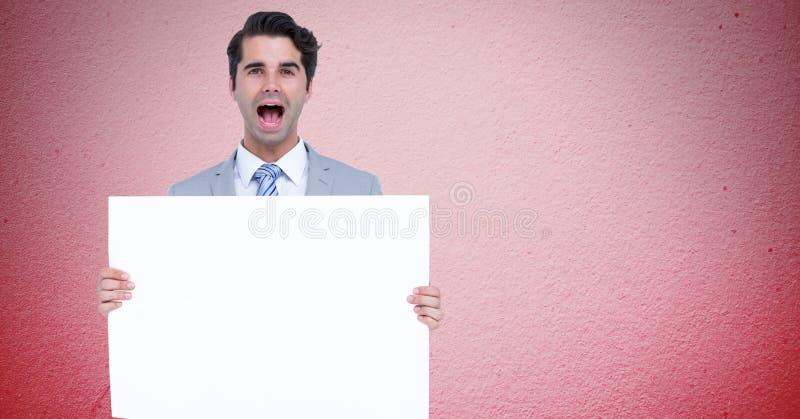 Retrato del hombre de negocios que grita mientras que sostiene la cartelera en blanco contra fondo rosado libre illustration