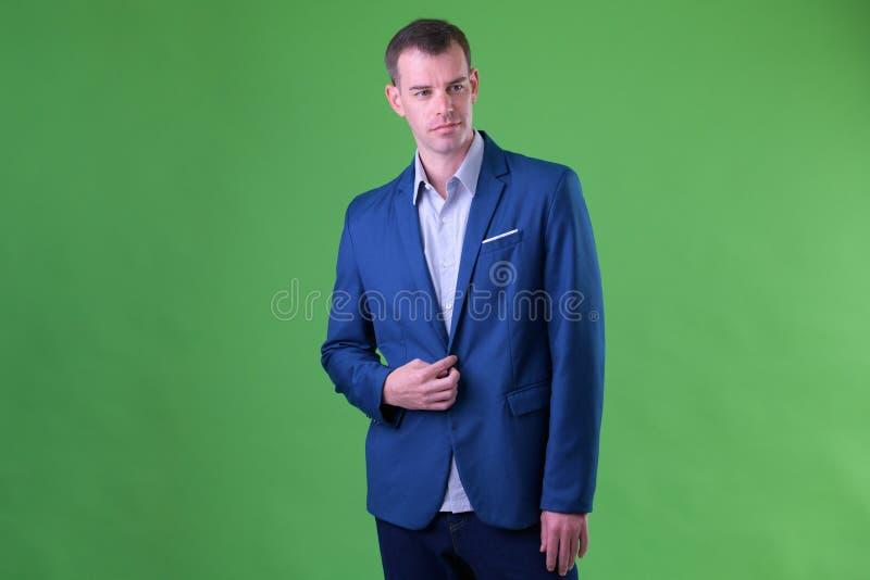Retrato del hombre de negocios que lleva el traje azul que mira la cámara fotografía de archivo