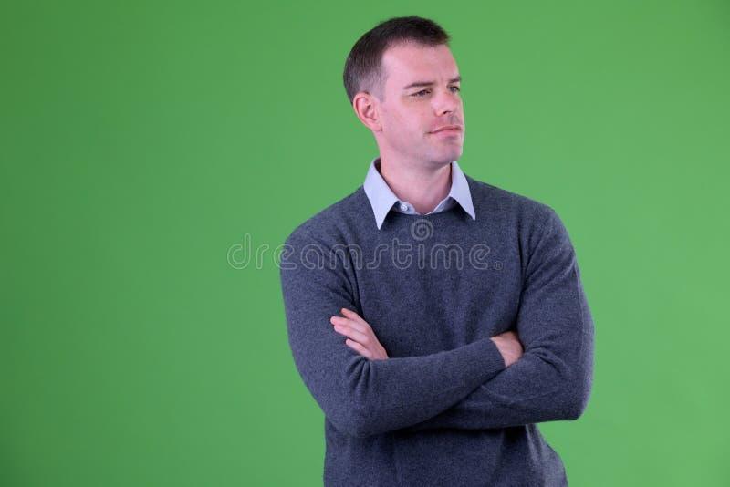 Retrato del hombre de negocios que piensa con los brazos cruzados contra fondo verde fotos de archivo libres de regalías
