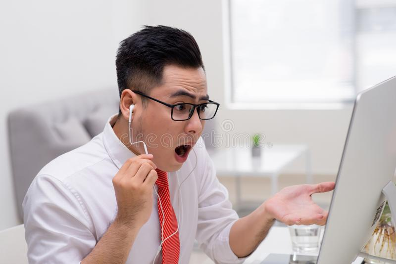 Retrato del hombre de negocios que se sienta en el escritorio de oficina y que tiene vídeo foto de archivo
