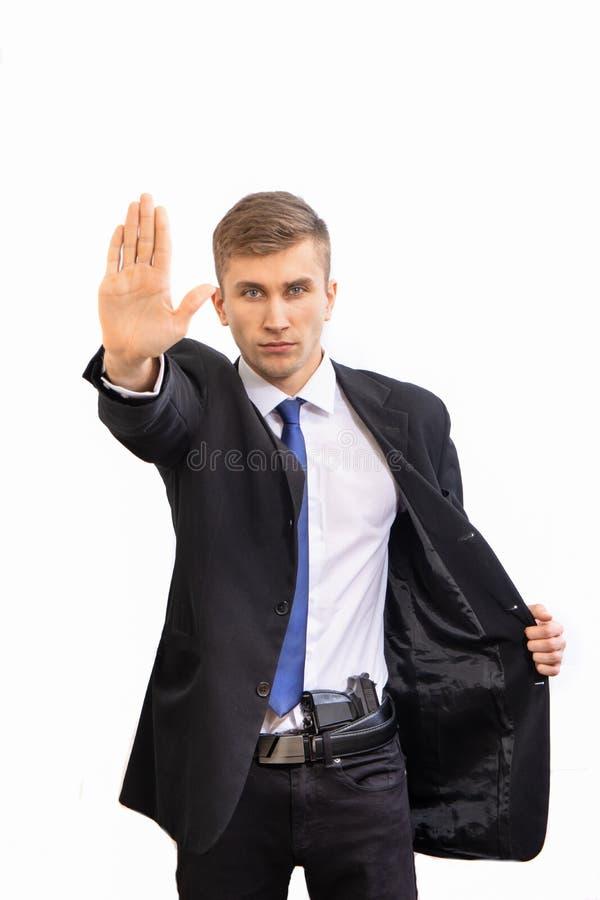 Retrato del hombre de negocios serio atractivo joven de seguridad con el arma en traje oscuro y lazo azul brillante, aislado en b foto de archivo libre de regalías
