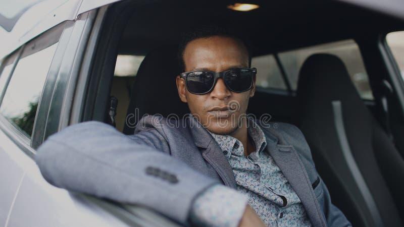 Retrato del hombre de negocios serio en las gafas de sol que se sientan dentro del coche y que miran en cámara al aire libre foto de archivo