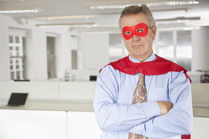 Retrato del hombre de negocios serio en traje del super héroe en oficina imagen de archivo libre de regalías
