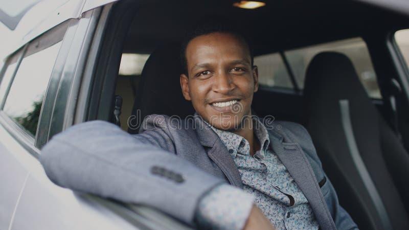 Retrato del hombre de negocios serio que se sienta dentro del coche y que sonríe en cámara al aire libre imágenes de archivo libres de regalías