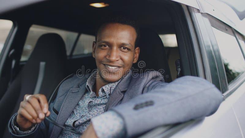 Retrato del hombre de negocios serio que se sienta dentro del coche y que sonríe en cámara al aire libre foto de archivo