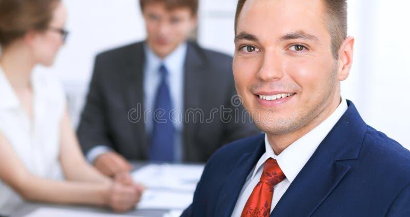 Retrato del hombre de negocios sonriente alegre contra un grupo de hombres de negocios en una reunión foto de archivo libre de regalías