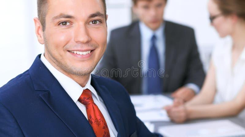 Retrato del hombre de negocios sonriente alegre contra un grupo de hombres de negocios en una reunión imagen de archivo libre de regalías