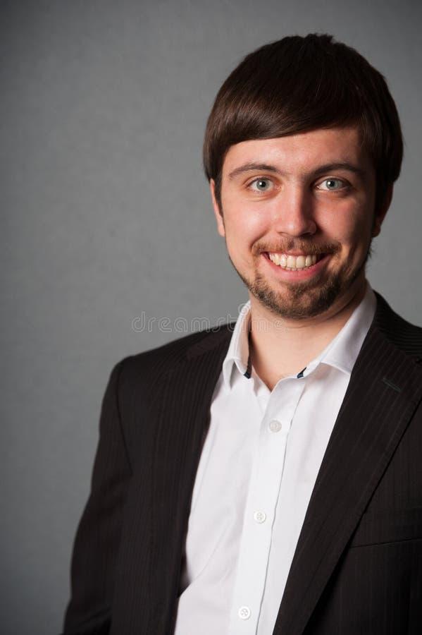 Retrato del hombre de negocios sonriente en fondo gris imagen de archivo libre de regalías