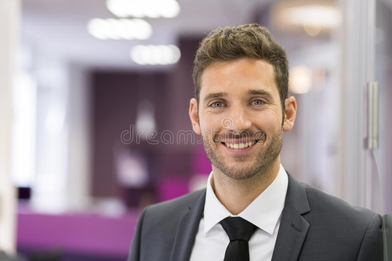 Retrato del hombre de negocios sonriente que presenta en la oficina moderna, lookin imagen de archivo
