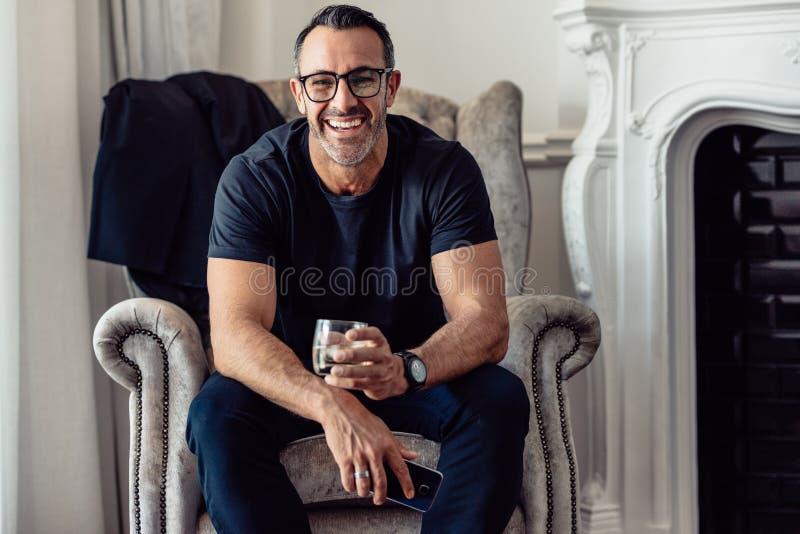 Retrato del hombre de negocios sonriente que se sienta en la habitación con el teléfono y el vidrio de la bebida que miran la cám fotos de archivo